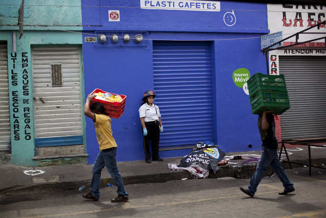 Personas pasan junto al  cadáver de Alberto Archila, asesinado el viernes, en la calle en Ciudad de Guatemala, mientras se cumple la diligencia judicial respectiva.