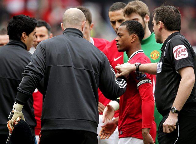 Patrice Evra (segundo desde la derecha) permanece con su diestra extendida ante Luis Suárez (izq.) en el partido del sábado.