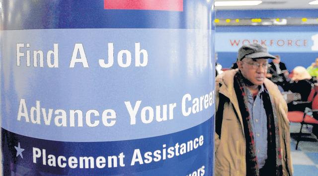 Un hombre pasa al lado de un cartel en el que se detallan los servicios que presta el centro de desempleo (Workforce1 Career Center) en Brooklyn.