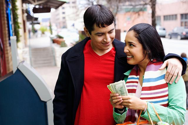 Una pareja cuenta el dinero recibido por un trabajo hecho en casa