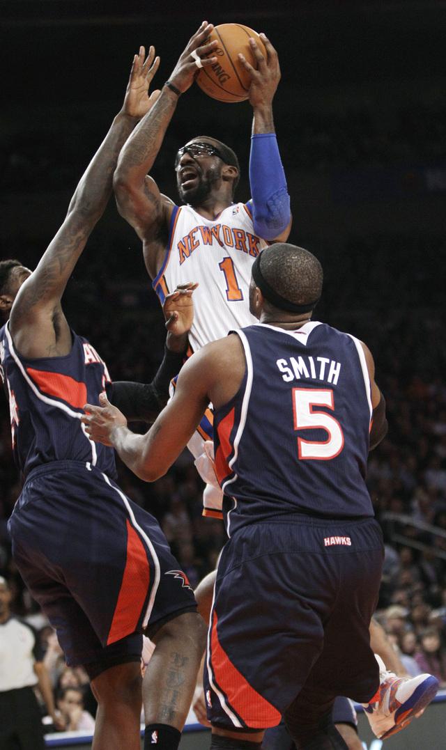 Amare Stoudemire, de los Knicks, se eleva hacia el canasto entre Marvin Williams (izq) y Josh Smith (der.) de los Hawks durante el partido de anoche en el Garden.