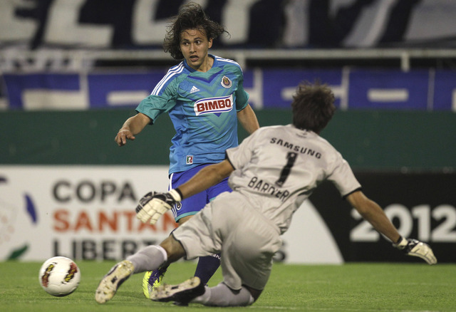 Omar Arellano, de las Chivas (de frente) intenta burlar al portero de Vélez Sarsfield, Marcelo Barovero, en el partido que se efectuó  ayer en Buenos Aires.