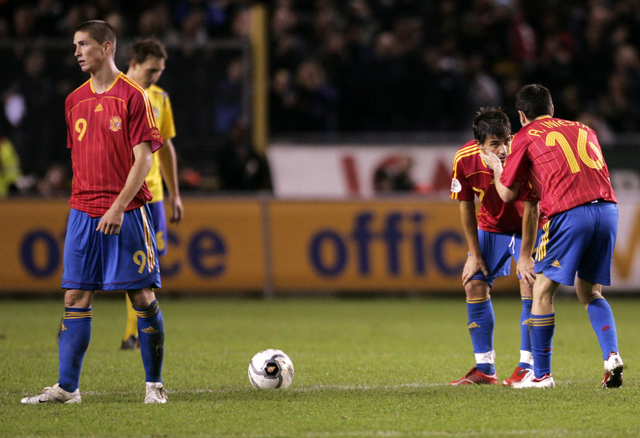 Andrés Iniesta (d) consuela a sus compañero David Villa, mientras Fernando Torres (izq) sabandona el campo de juego tras una derrota de España ante Suecia en la fase calificatoria a la Eurocopa 2008, que terminó ganando.
