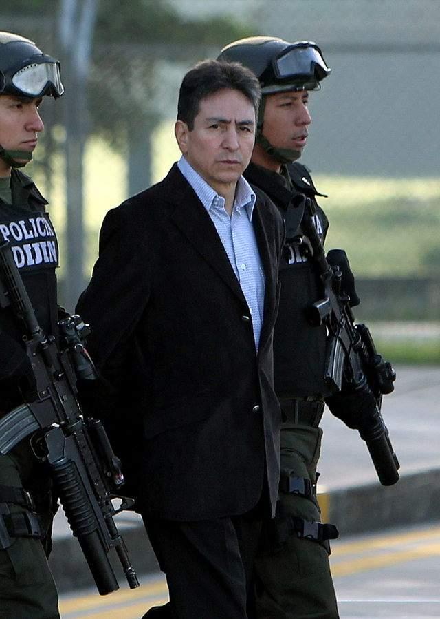 """Policías custodian a Danilo Bustos Suárez (c), sindicado de ser el socio estratégico de Daniel Barrera Barrera, alias el """"Loco Barrera""""."""