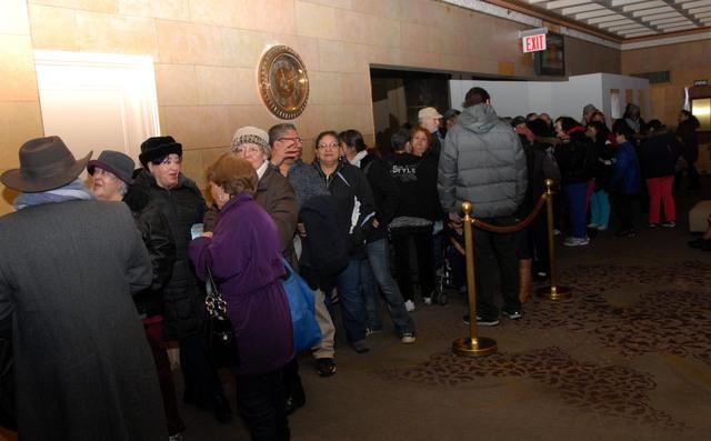 """parte de las numerosas personas que hicieron fila en el Hotel Affinia para recibir alimentos, bajo el programa """"Thanksgiving in February""""."""