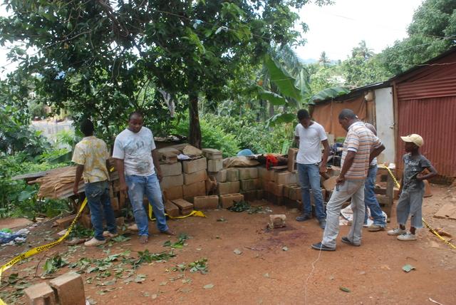 Familiares y vecinos del exmilitar fallecido lloran y ven los residuos dejados por la explosión de la granada durante hechos ocurridos en  Villa Altagracia.