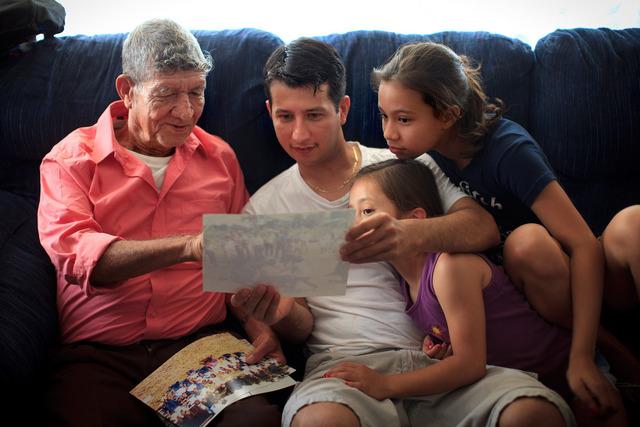 Tranquilino Castañeda muestra fotos de su pueblo natal a su hijo Oscar  Ramírez y a sus nietas Nicole y Andrea el 29 de mayo en    Framingham, Massachussetts.