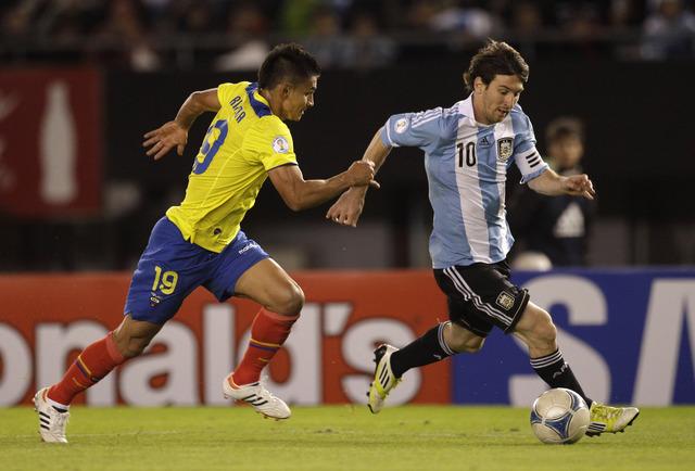 Lionel Messi (der.) esquiva la marca del ecuatoriano Fernando Saritama durante el triunfo de Argentina por 4-0.