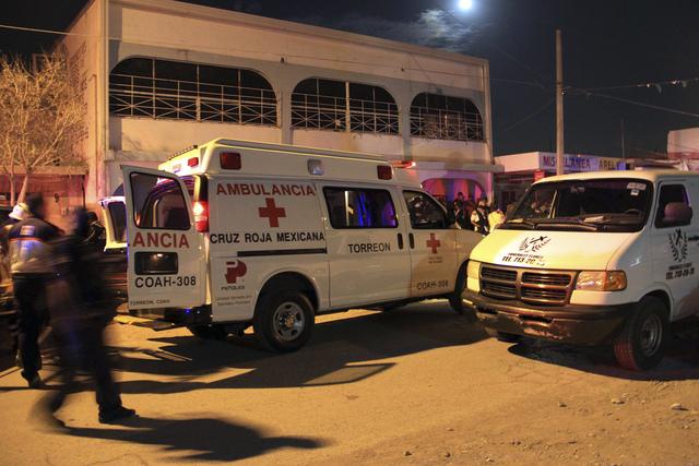 """Ambulancias permanecen frente al edificio del centro de rehabilitación """"Tu Vida sobre la Roca"""" en la ciudad de Torreón, donde fueron asesinadas a tiros 11 personas y al menos ocho  quedaron heridas."""