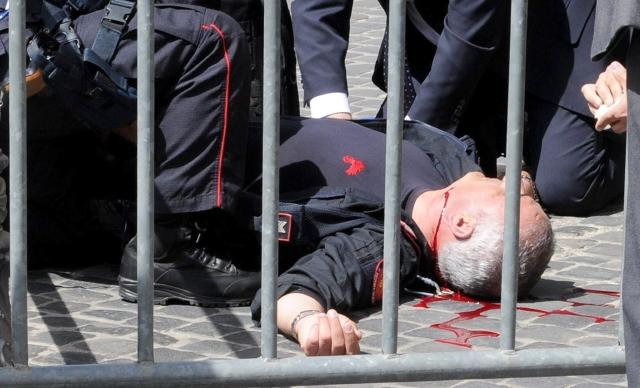 Compañeros prestan ayuda a un  carabinero  que resultó herido en  en un tiroteo ayer en las afueras del Palacio Chigi,  en Roma, donde se produjo un tiroteo.
