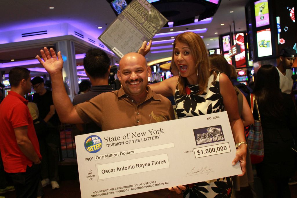 El premiado junto a Yolanda Vega, portavoz de la Lotería de Nueva York.