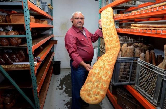 Rafael Eduardo se enorgullece de su pan pizza romana, que mide 72 pulgadas de largo.