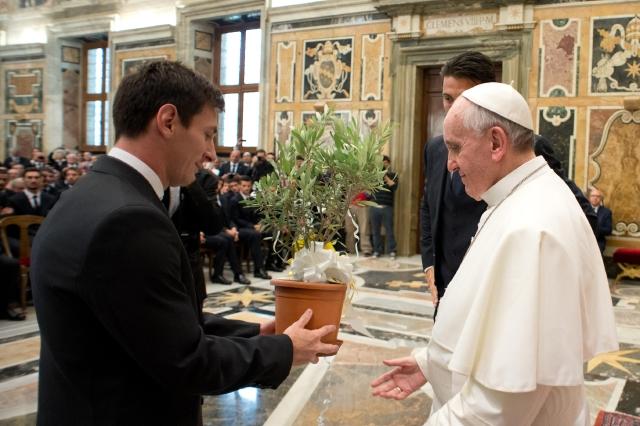 El papa Francisco recibe un regalo del astro Lionel Messi durante una audiencia privada del seleccionado albiceleste en el Vaticano.