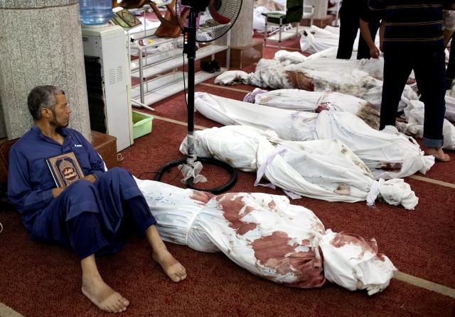 Un hombre sostiene una copia del Corán sentado junto a docenas de cadáveres en la mezquita al-Imene en El Cairo, Egipto.