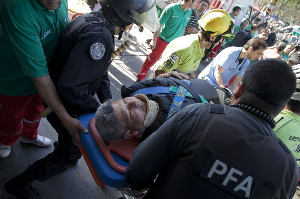 Los socorristas cargan a uno de los 99 heridos del accidente de tren en la estación Once.