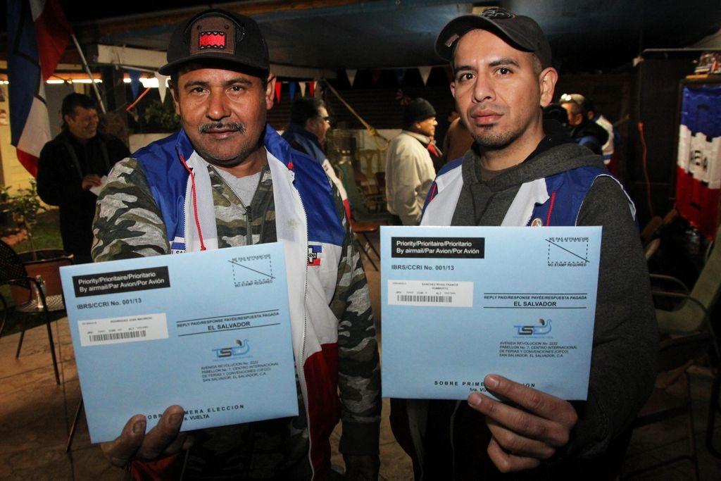 Los salvadoreños José Rodríguez (izq.) y Francisco Sánchez muestran los sobres preparados con sus papeletas de votación a las elecciones presidenciales de su país.
