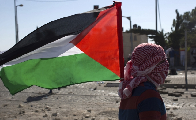Un joven ondea una bandera palestina durante un enfrentamiento contra las fuerzas israelíes en el barrio de Shuafat.