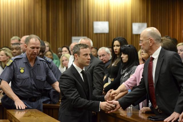 Policías escoltan a Oscar Pistorius (c) quien se despide de sus familiares antes de ser trasladado a  la cárcel    para purgar cinco años por matar a su novia Reeva Steenkamp.