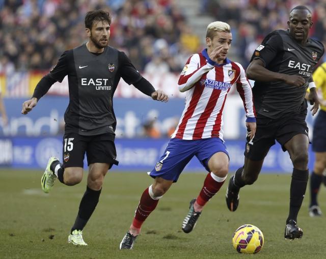 Antoine Griezmann, autor de dos goles, (centro) escapa a la vigilancia del defensor del Levante, Nikos Karabelas durante el partido de ayer en el Estadio Vicente Calderón.