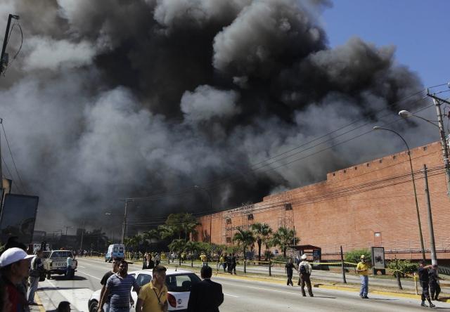 Personal del cuerpo de bomberos salvadoreños trataban de controlar el incendio ayer en el centro comercial.