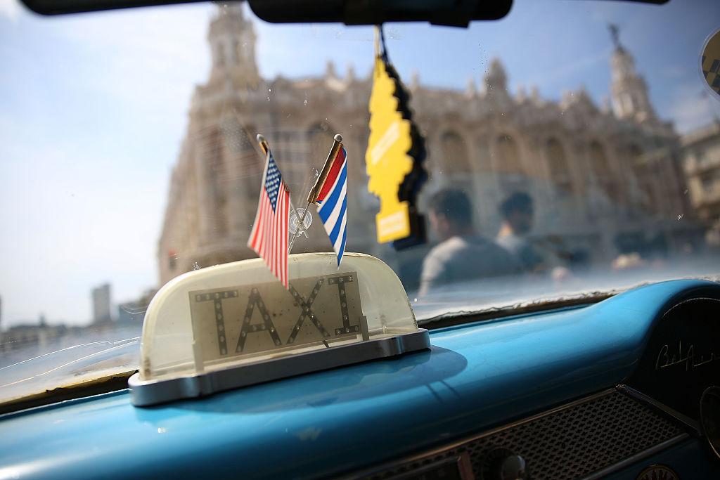 Las banderas de Cuba y Estados Unidos ondean en el interior de un taxi en La Habana.