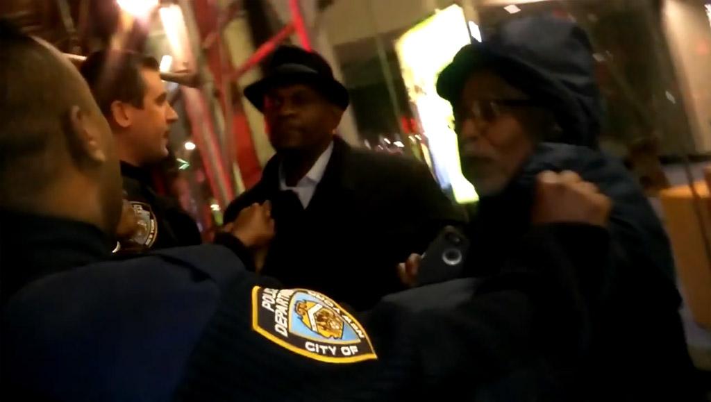 Mualimm-ak, con sombrero, junto a los policías durante el forcejeo.