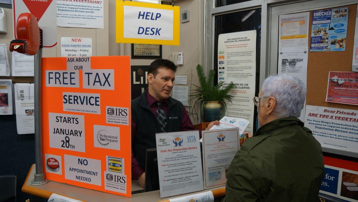 Thomas Neve, director ejecutivo y fundador de Reaching-Out Community Services (Brooklyn) entrega información a usuarios del food pantry sobre el programa gratuito de asesoría de impuestos.