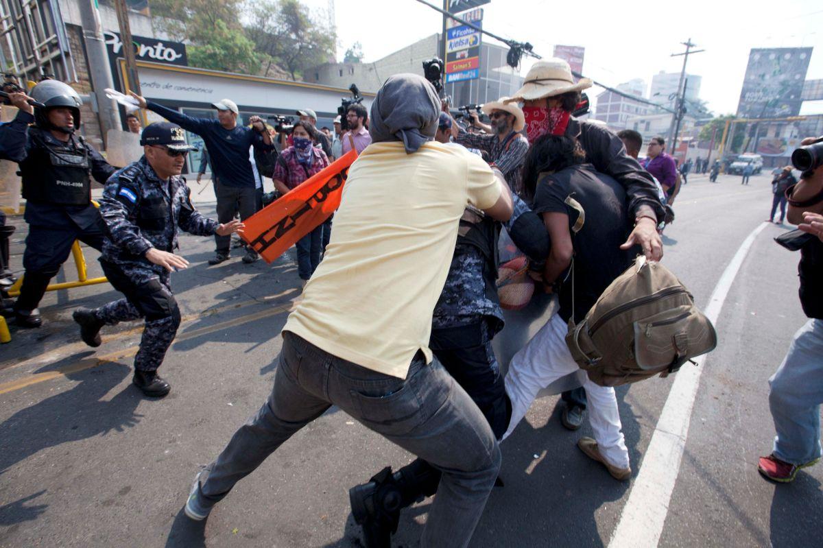 Policías antimotines hondureños desalojan una manifestación de pobladores indígenas lencas que se encontraban frente a la Casa Presidencial en Tegucigalpa.