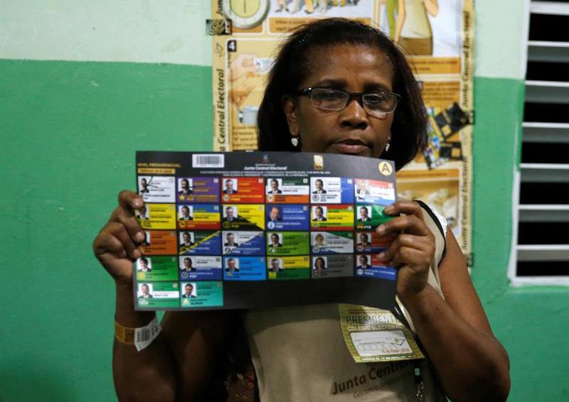 Una vocal de una mesa de votación sostiene un voto durante el conteo tras el cierre de los colegios en Santo Domingo.