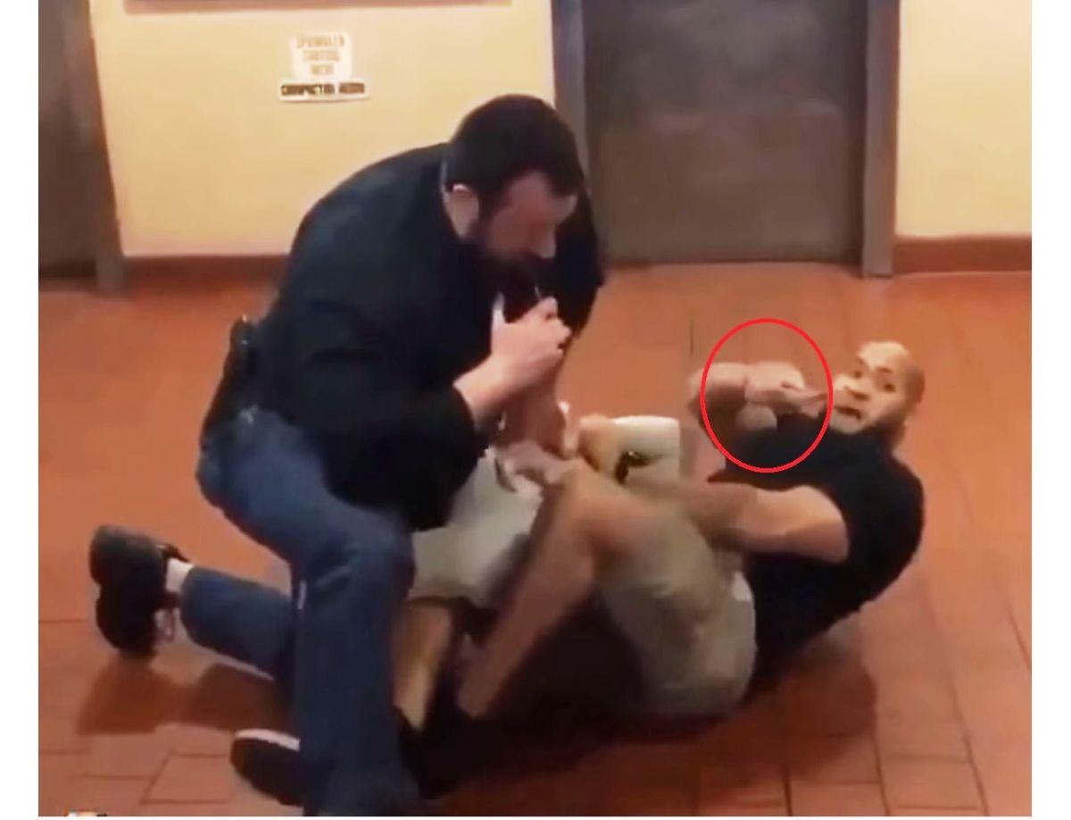 Momento en que el agente Risel Martínez saca el arma