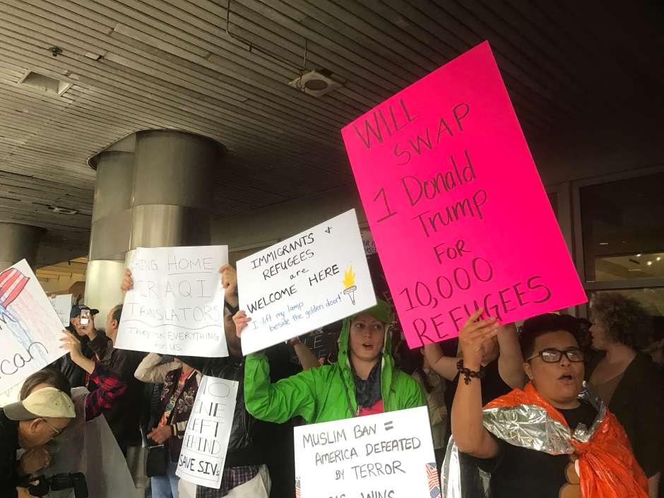 Centenares protestan en aeropuertos de Florida contra el veto temporal decretado por Trump.