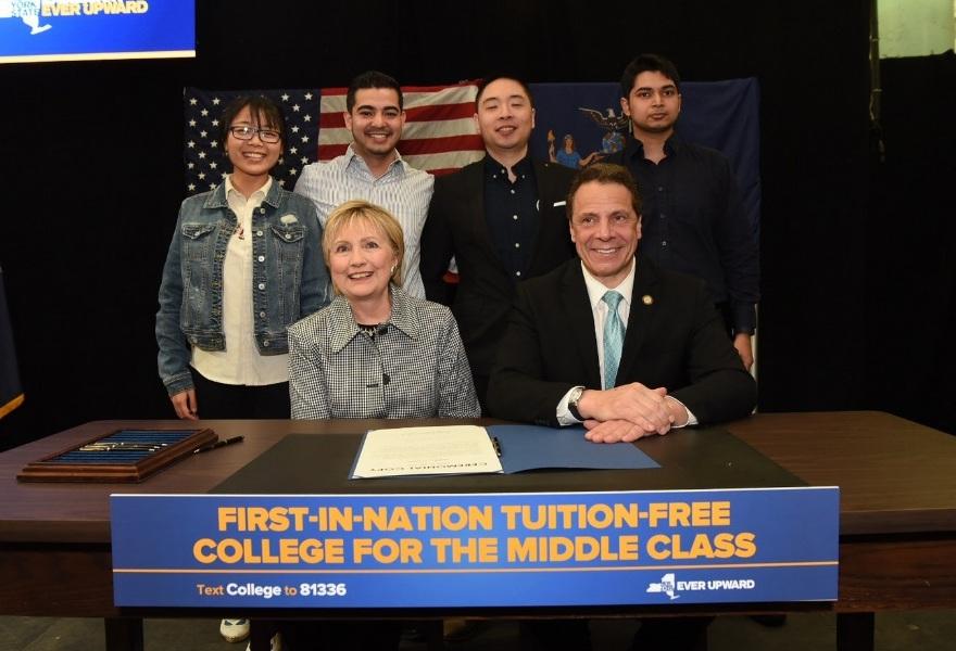 Hillary Clinton, y jóvenes que se beneficiarán, acompañaron al gobernador Andrew Cuomo en la firma de la ley.