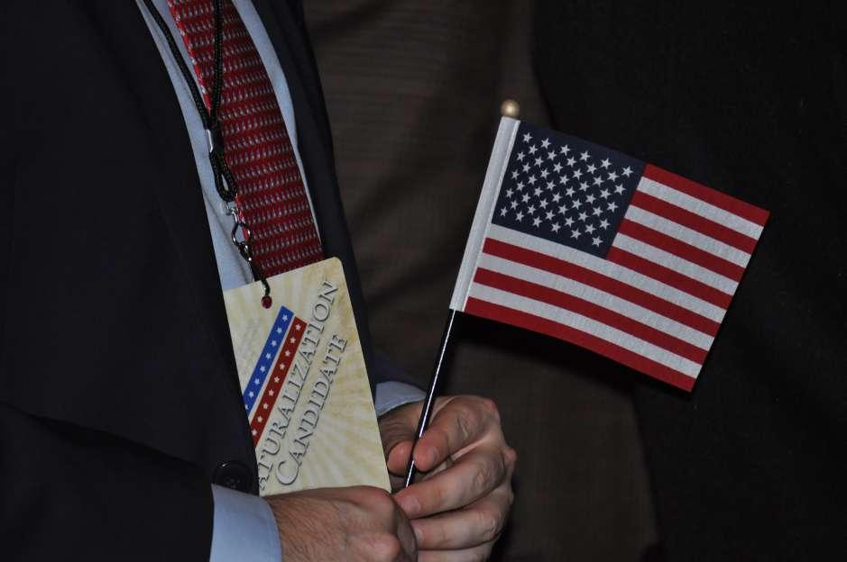 Uno de los nuevos ciudadanos estadounidenses sujeta una bandera de Estados Unidos en la ceremonia de naturalización 10 de abril en el edificio del New-York Historical Society
