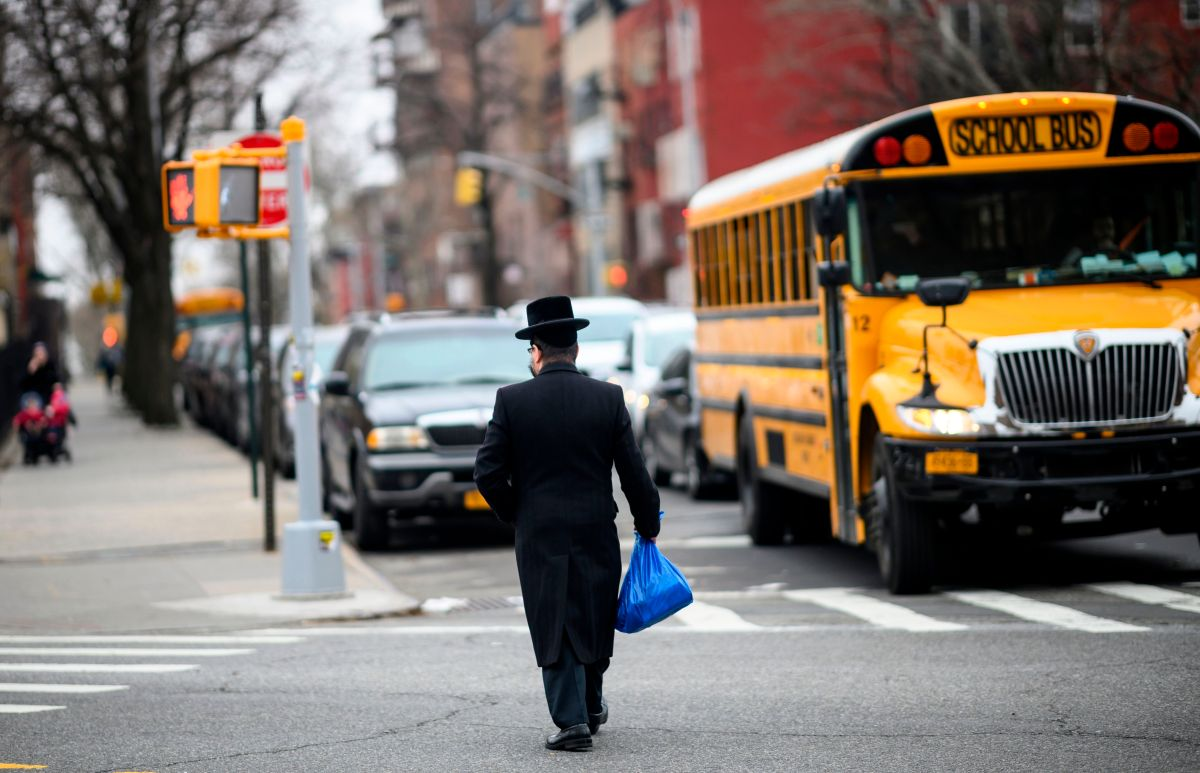 A Jewish man crosses a street in a Jewish quarter in Williamsburg Brooklyn on April 9, 2019 in New York City. - New York Mayor Bill de Blasio declared a public health emergency across part of Brooklyn, ordering all residents receive the measles vaccine in a bid to contain an outbreak of the disease. In New York, an Orthodox Jewish community in Brooklyn has been hardest hit. They were infected by visitors from Israel, where an outbreak of measles began a year ago. (Photo by Johannes EISELE / AFP)        (Photo credit should read JOHANNES EISELE/AFP/Getty Images)