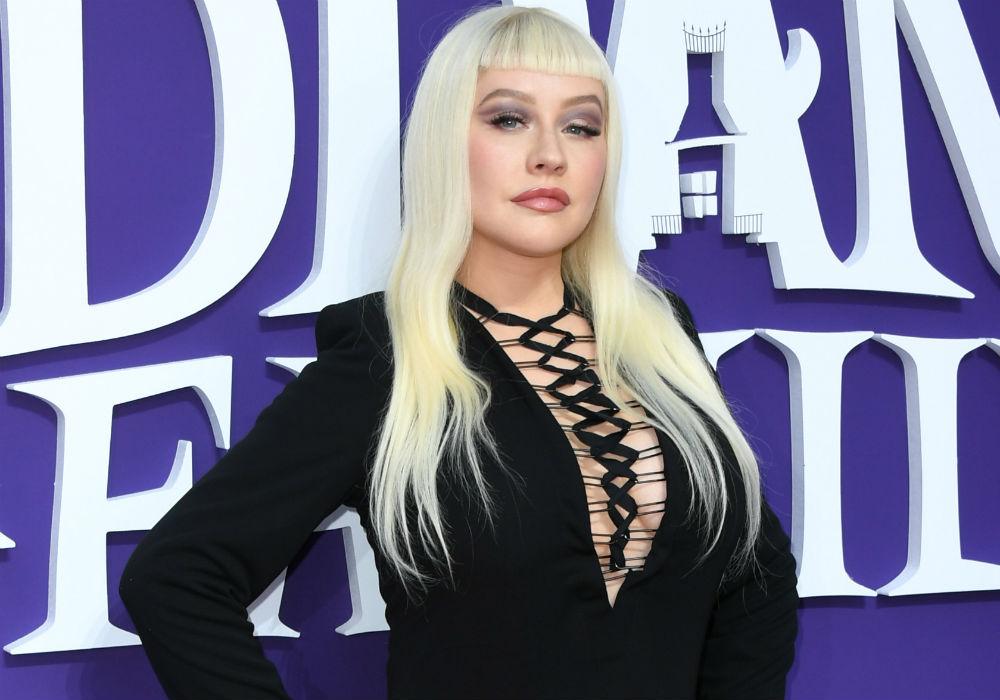 Christina Aguilera posa junto a Karol G  y ¡disfraza a su familia como Los Locos Addams!