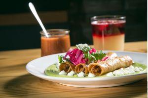 ¡El antojo mexicano perfecto! Exquisitos tacos dorados de res ahogados en salsa cremosa de aguacate