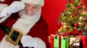Santa Claus dentro de un globo plástico y detrás de una barrera de pexiglás por el coronavirus