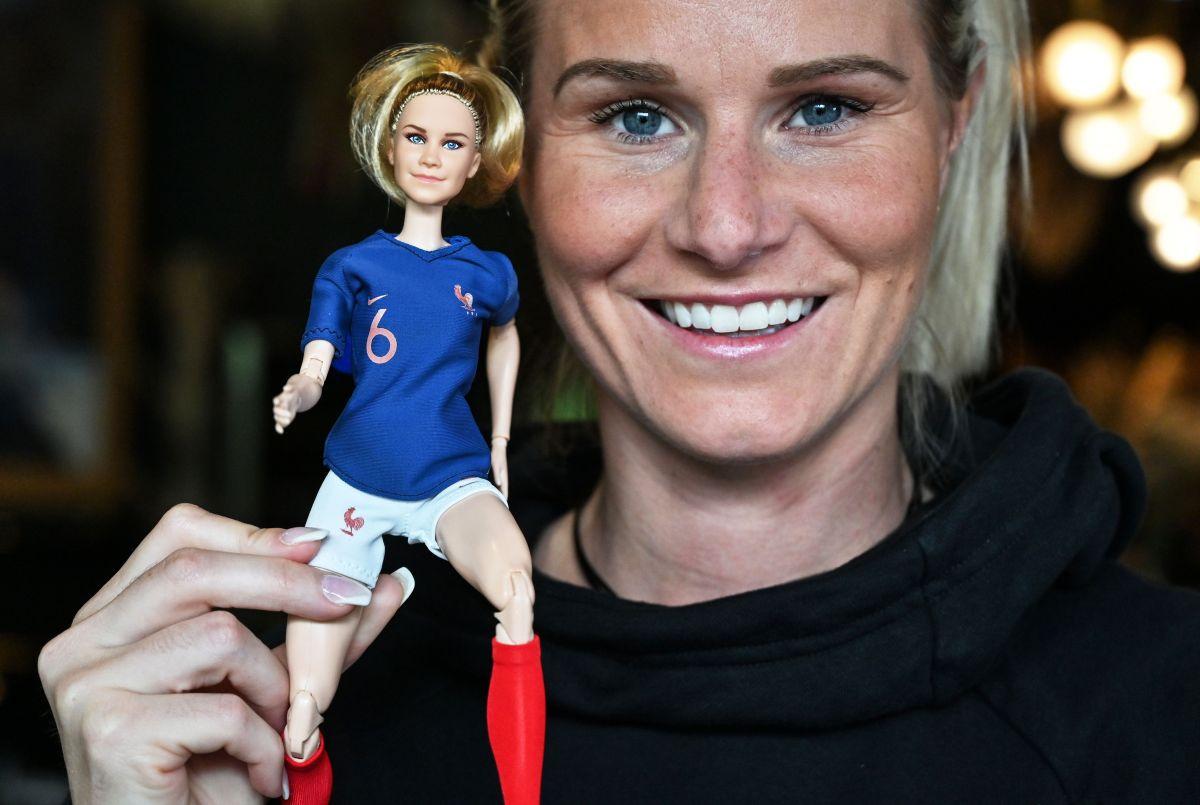 La futbolista Amandine Henry sostiene la muñeca que inspiró.