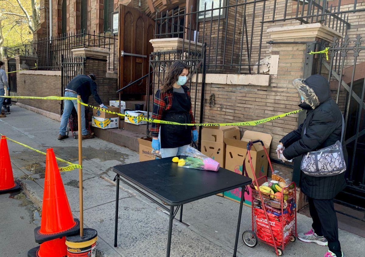 Una mujer llena su carrito con comida en una despensa de alimentos en Chelsea, donde esta semana se registraron largas filas de personas necesitadas.