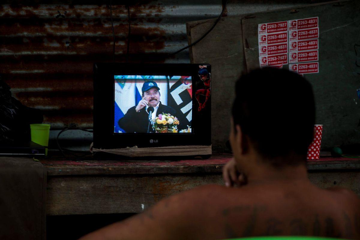 Un hombre observa la pantalla de un televisor en donde aparece el presidente de Nicaragua, Daniel Ortega.