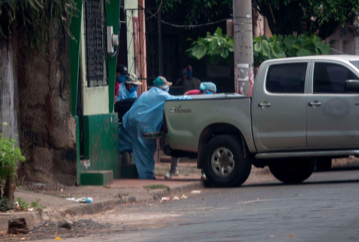 Trabajadores cargan un ataúd en una camioneta en Chinandega.