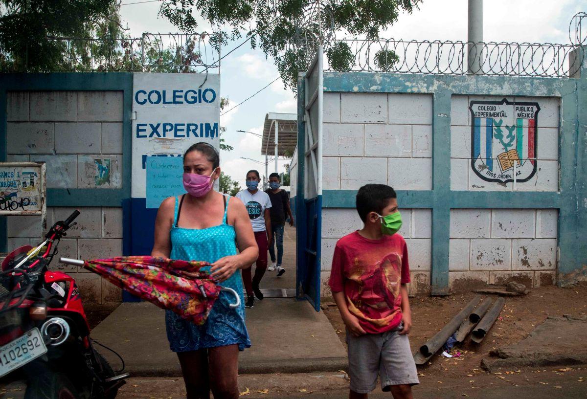 Una mujer junto a su hijo (d) utilizan tapabocas al salir de una escuela pública este viernes, en Managua.