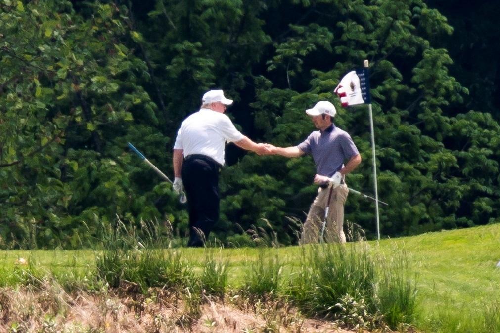 Trump saluda de mano a un hombre en el club de golf.