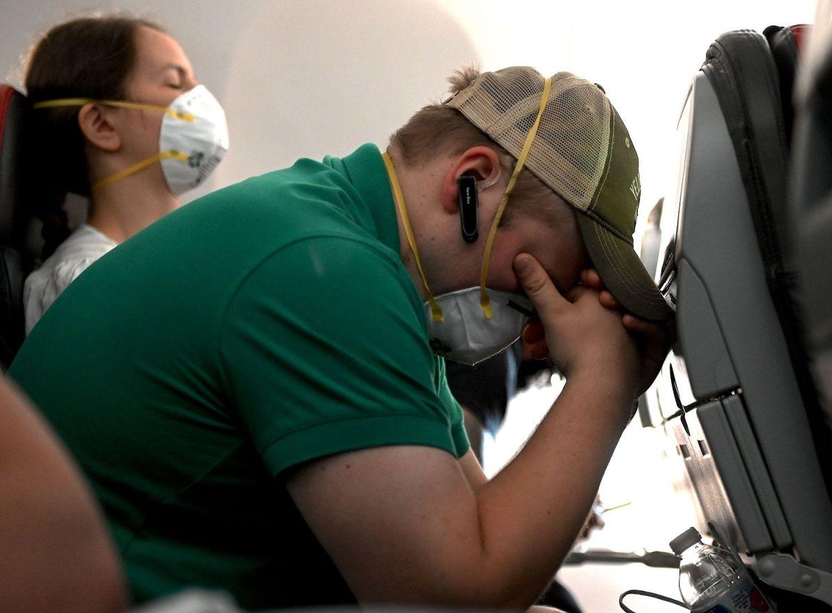 Pasajeros de un vuelo doméstico en Estados Unidos usan mascarillas durante el viaje.