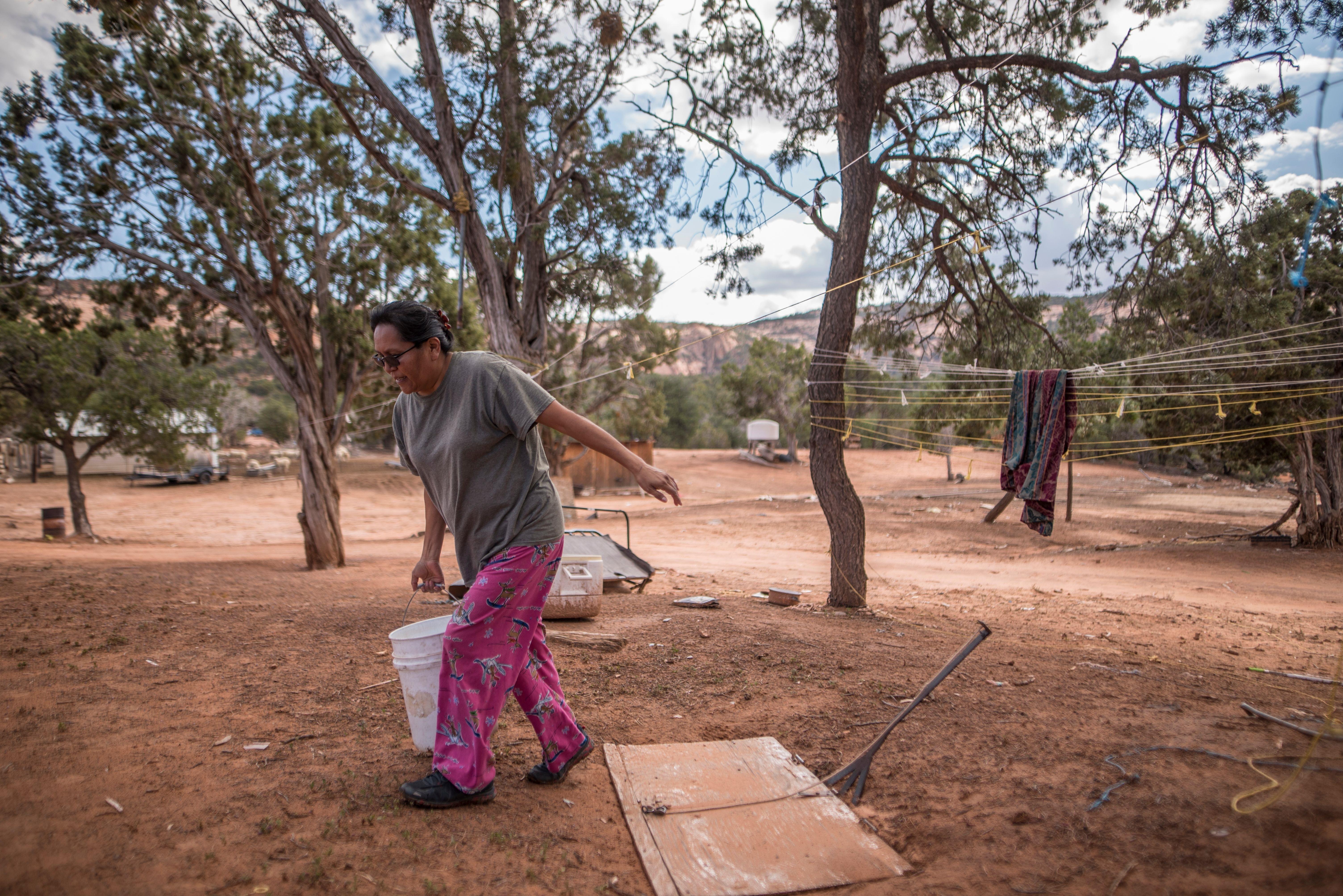 Una mujer navajo llevando un cubo de agua en Navajo Montain.