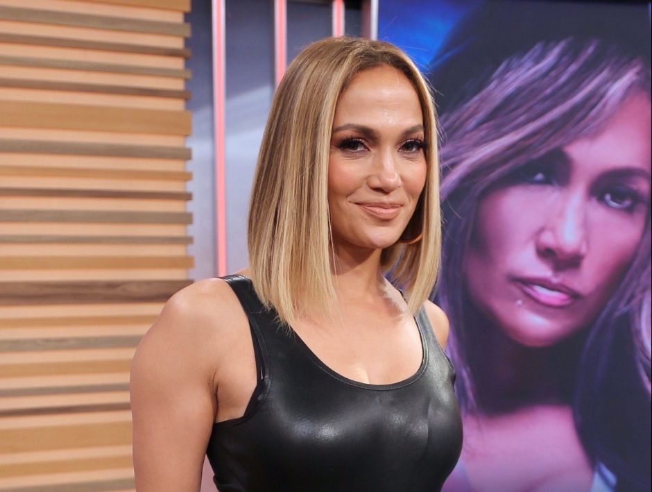 Jennifer Lopez posa al pie de la cama, usando una blusa blanca transparente