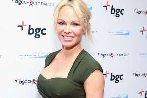Usando lencería negra con liguero y en una atrevida pose, Pamela Anderson modela en la cama