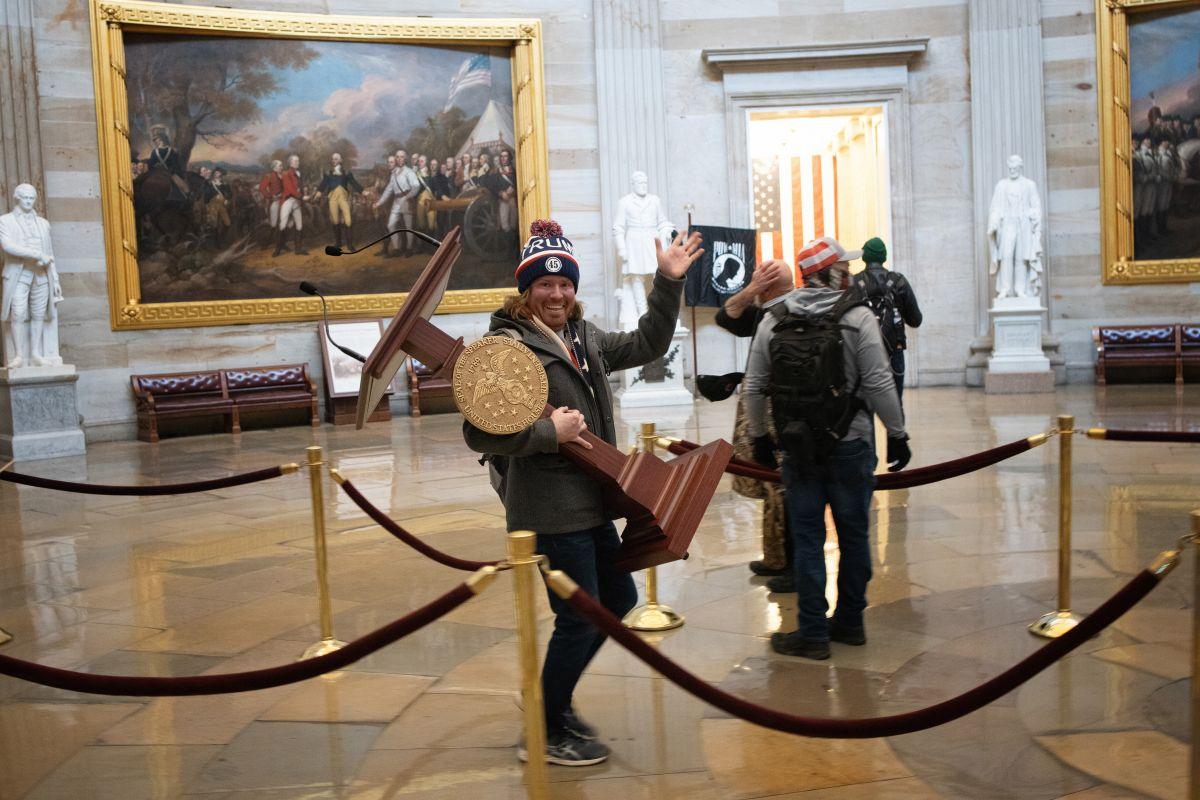 La imagen del fotógrafo Win McNamee ha dado la vuelta al mundo cuando un hombre carga un atril del Congreso.