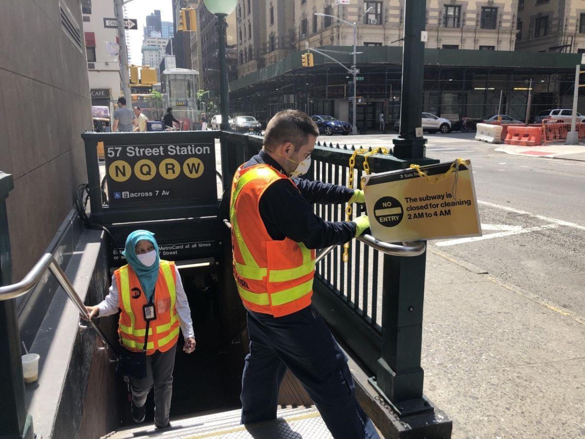 Trabajadores de la MTA retiran los carteles que anunciaban el cierre nocturno del Metro de la ciudad de Nueva York.