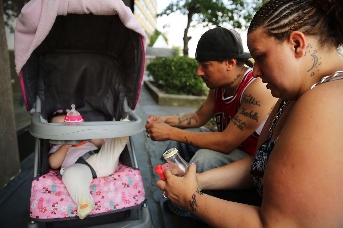 Una familia hispana desamparada sentada afuera de un refugio en Queens. La nueva ley busca que más personas dejen los albergues de la Ciudad.